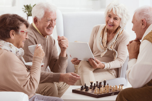 four older adults playing chess